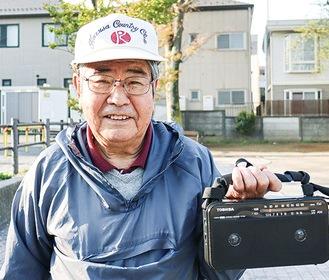 3代目のラジオを手に笑顔の原さん