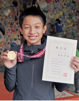 メダルと賞状を手に笑顔の福本君