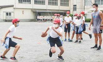 選手に教わりながらアメフットを体験する児童ら