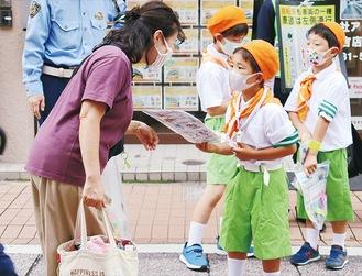 歩行者に啓発グッズを手渡す児童