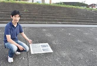 跡地で記念プレートを指さす小林さん