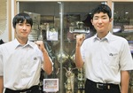 過去の賞杯の前に立つ、高木部長(右)と市川主将