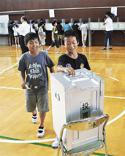 実際の投票箱に用紙を入れる児童
