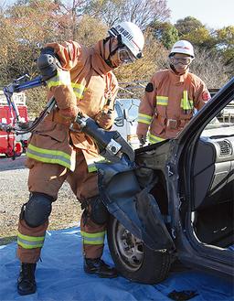 大型油圧救助器具で車体を破壊する隊員
