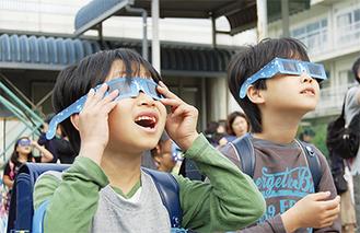 日食を観察する児童ら