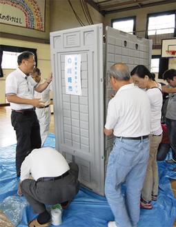仮設トイレを組み立てる参加者
