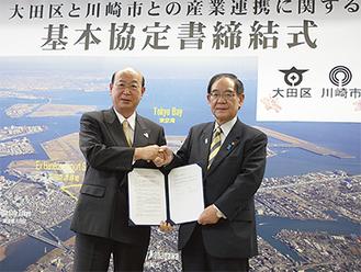 ▲協定書を手に握手する阿部市長(右)と松原区長