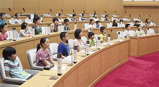 議員席に座って議長らの話を熱心に聴く児童