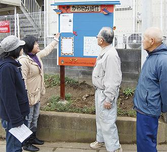 掲示板を地元の人々に披露する実行委員ら