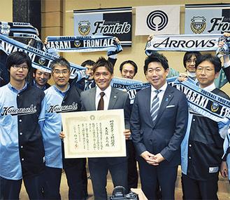 サポーターに囲まれて笑顔を見せる大久保選手(中央)と福田市長(中央右)/川崎市役所で