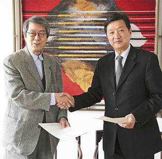 握手を交わす日本映画大の荒井晴彦教授(左)と北京電影学院のチャン・フイジュン院長