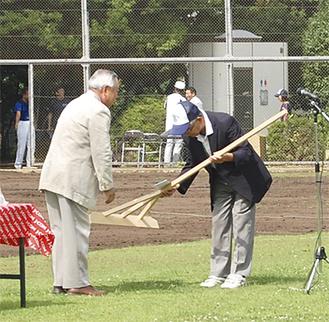 区少年野球連盟小林時治会長(右)にトンボを手渡す梅澤会長