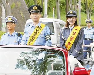 オープンカーに乗り、パレードする曽田さん(右)と川田署長