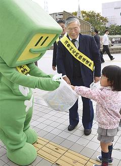 カマキリ広場を通った児童(右)に啓発資料を配るイータ君と川崎西間税会の梶会長(中央)