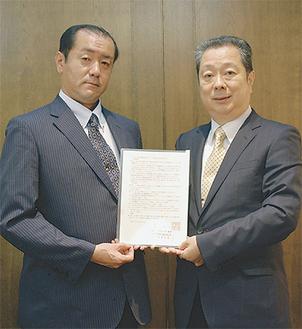 川崎市との協定書を持つ鳥海理事長と飛鳥典禮の真鍋康行代表取締役(左)