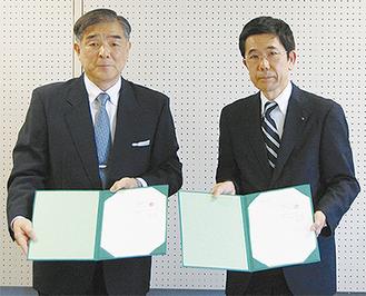 調印式で協定書を交わす伊東達夫学長(左)と中島理事長