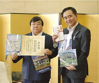 ファイルを披露した伊坂会長(左)と黒岩県知事