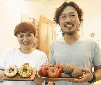 生産農家の井上さん(右)と新メニューを手にする伊藤店長(左)