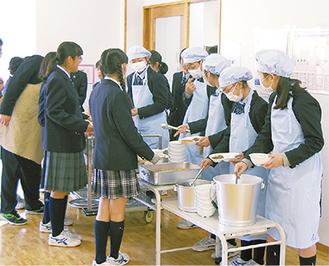 給食の盛り付けを行うはるひ野中の生徒ら