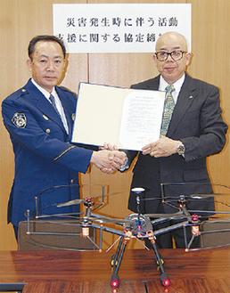 握手する古澤社長(右)と田中署長(左)