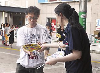 啓発物を配布する参加者(右)