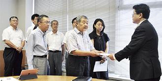 伊藤副市長(右)に申し入れ書を手渡す市民ネットワークのメンバー