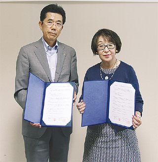 協定書を持つ生田学長(右)と中島理事長(左)