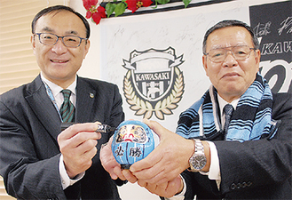 必勝だるまを持つ高桑会長(右)と藁科社長(左)