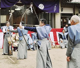 「歩射」で弓を引く保存会のメンバーら