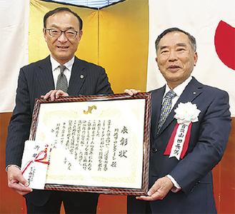 山田会頭(右)と表彰を受けた川崎フロンターレ藁科社長