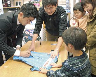 新ゆりグリーンプラザ商店会でレプリカユニフォームや優勝記念の冊子などにサインしていった谷口選手(写真左)