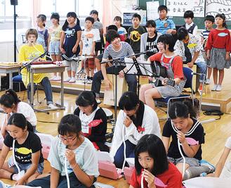 合奏するバンドの3人と児童