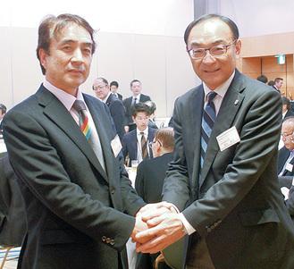 藁科代表(右)と握手する鴨志田会長(左)