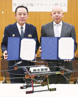 寄贈されたドローンを前に並ぶ田中署長(左)と古澤社長