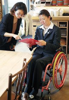 テーブルの高さを調べる成田さん(右)