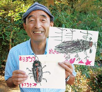 園児から届いた絵を手にする小島貢さん