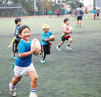 ボールを持ってグラウンドを走り抜ける子どもたち
