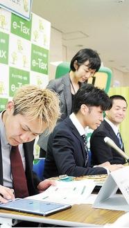 タブレットを操作して申告する古橋岳也選手(左手前)