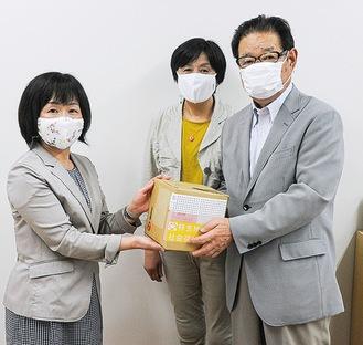消毒液を田中校長に手渡す久保倉会長(右)と吉垣君子委員長(中央)