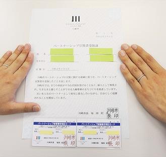 宣誓書受領証と受カードを手にする2人