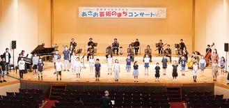 舞台に立つ少年少女合唱団=主催者提供