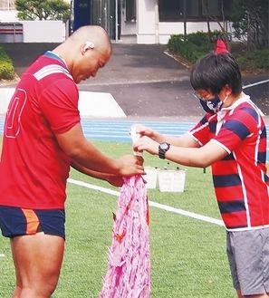 スクール生代表が千羽鶴を手渡す=3日、日大稲城グラウンド=同スクール提供