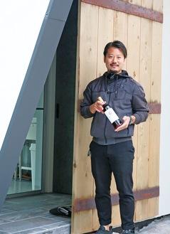 岡上に建設中の醸造所を前に立つ山田さん