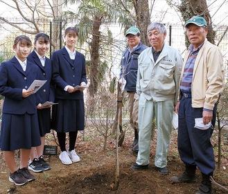 植樹した木を囲む飯草会長(右から2人目)ら保存会のメンバーと、山口さん(左から3人目)ら柿生中生徒