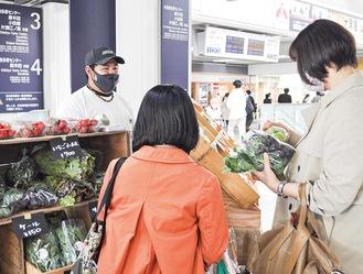 野菜を手に取り購入していく駅利用者