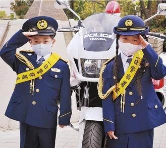 制服を着て敬礼をする篠原くん(左)と浅井さん