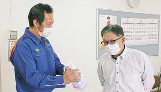 消毒用アルコールについて説明する同署員(左)