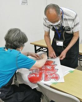 和凧の作り方を指導する同会メンバー(右)