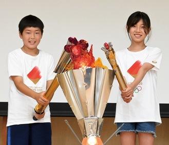 手作りトーチで聖火台に点火する阿部さん(左)と小川さん