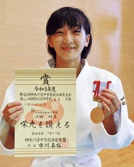 メダルと賞状を手にする沖田さん